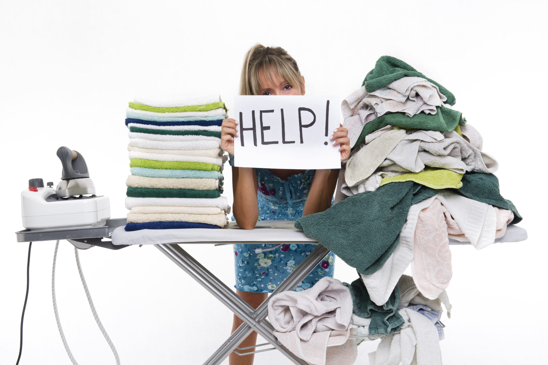 Woman behind a table covered with clothes to be ironed, displays a sign with help