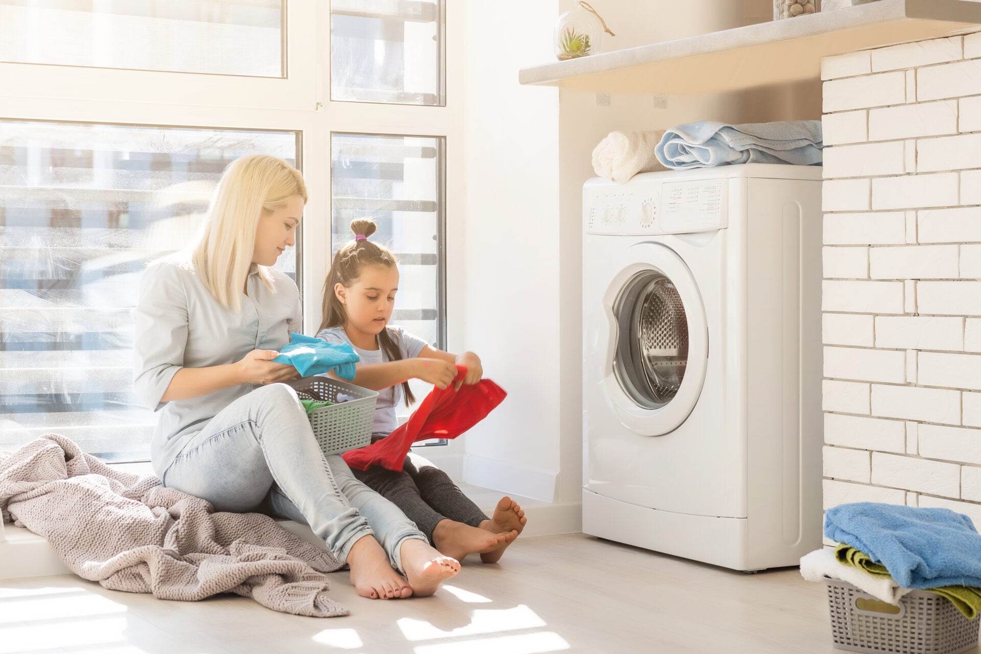 Happy housewife and her daughter with linen near washing machine