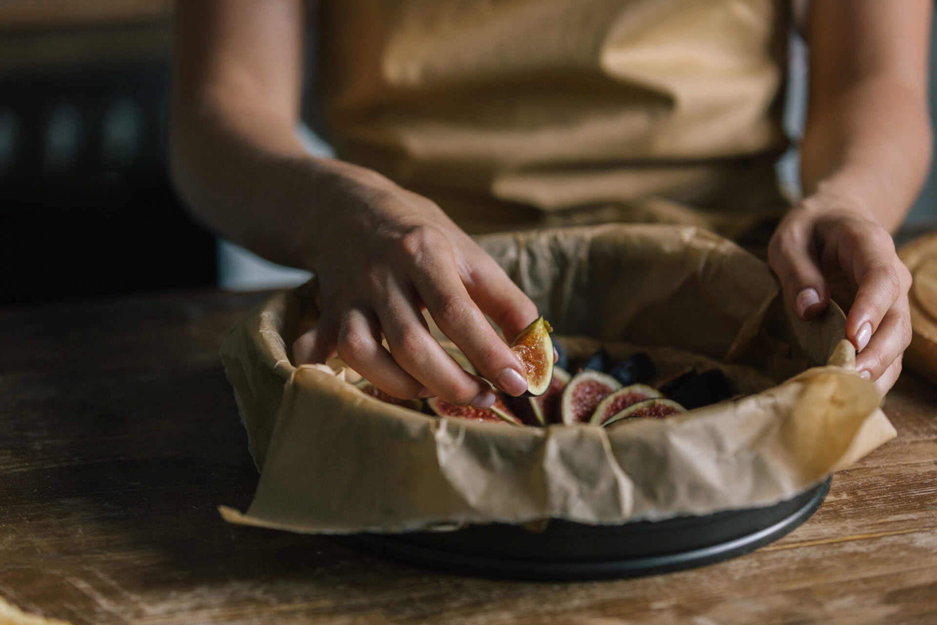 woman puts figs inside pie with parchment paper