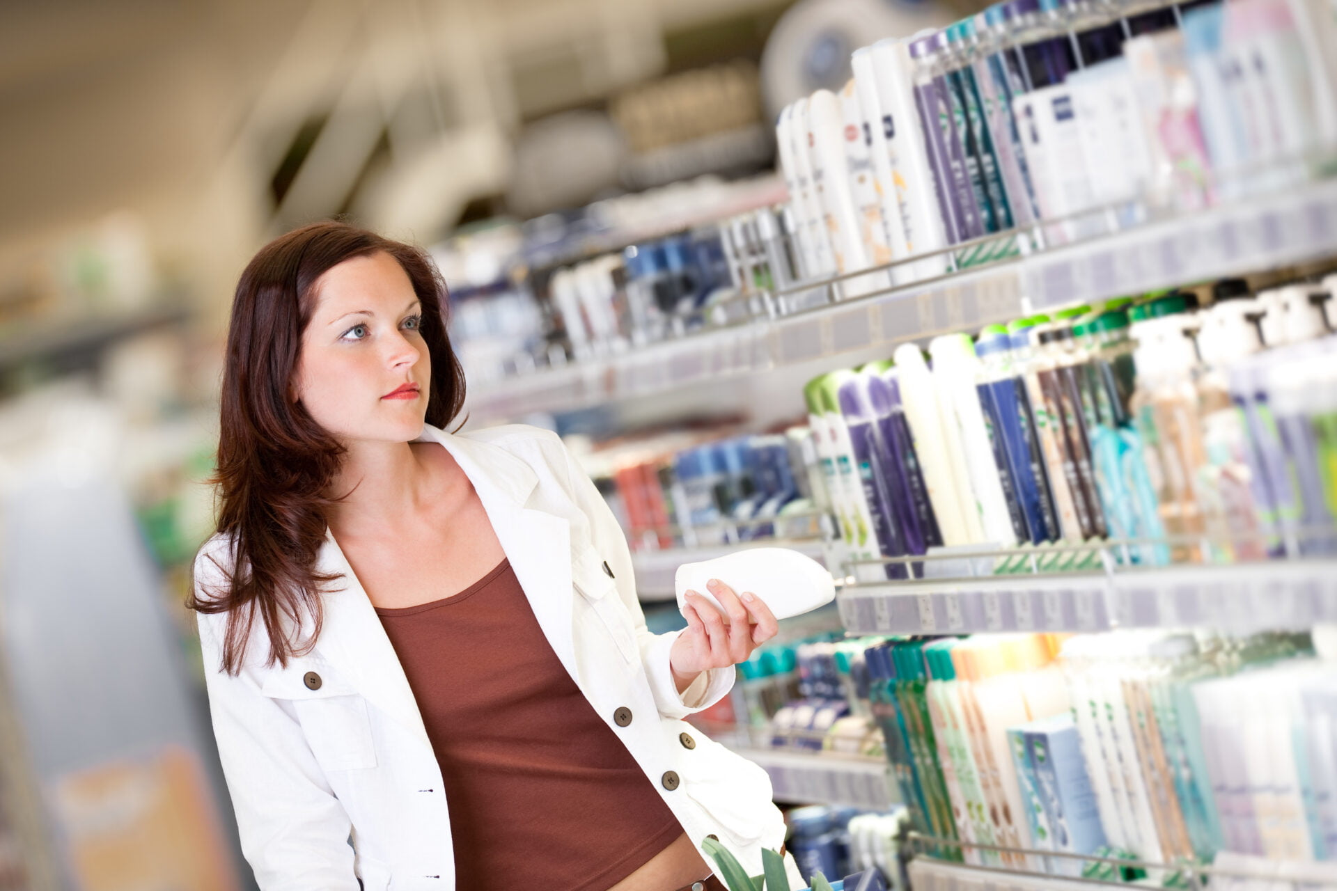 Young woman holding shampoo in cosmetics department