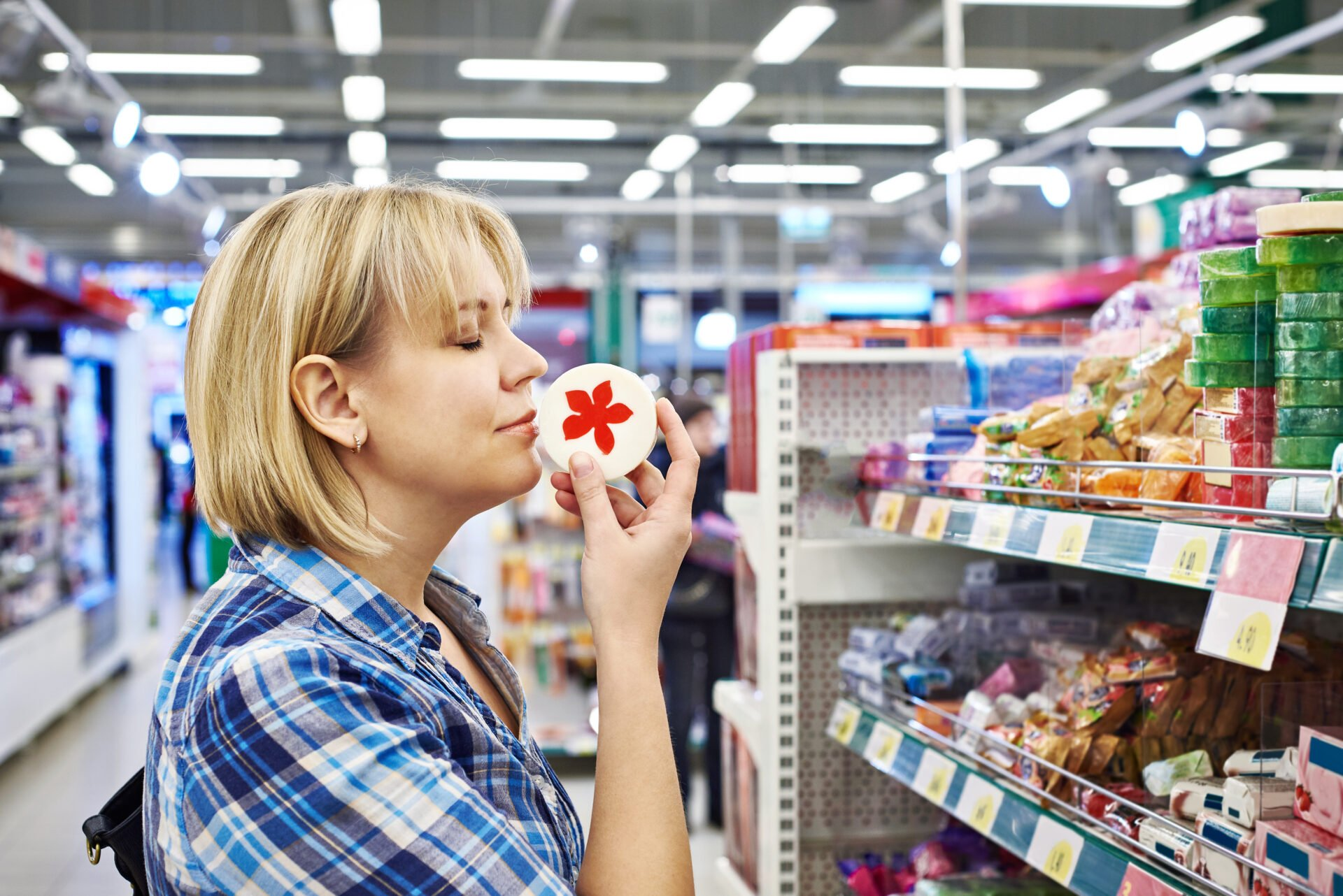 Woman smelling a fragrant soaps in the department of cosmetics