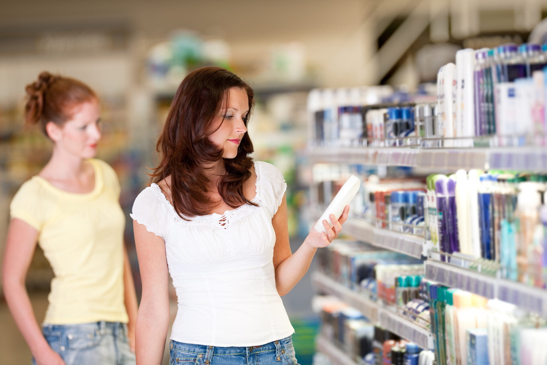 Woman checks out product in Target's clean beauty aisle