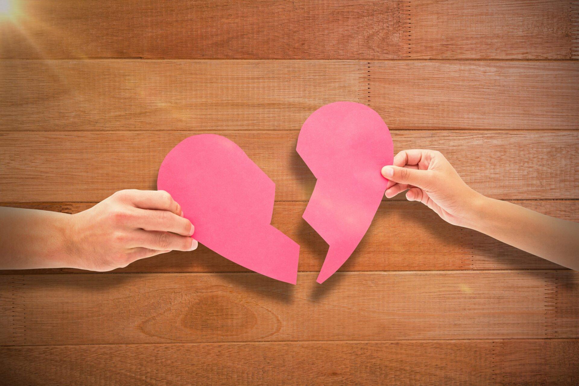 Hands holding two halves of broken heart against wooden floor
