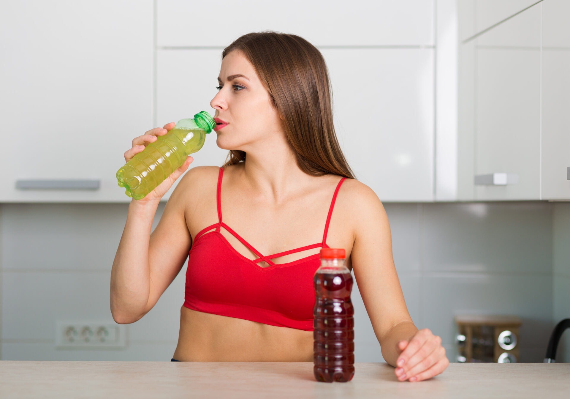 Woman holding two bottles of energy drinks