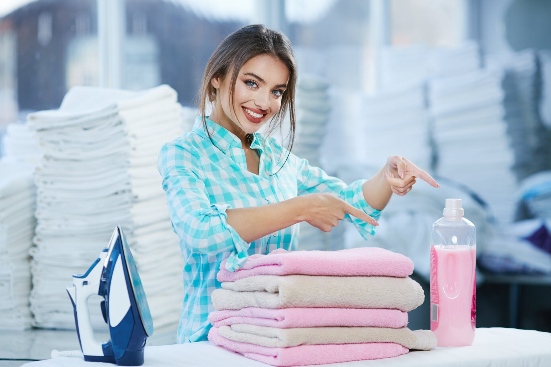 Woman standing near heap of rose towels and smiling. Woman near ironing board and detergent, heaps of white linen behind. Girl pointing at detergent