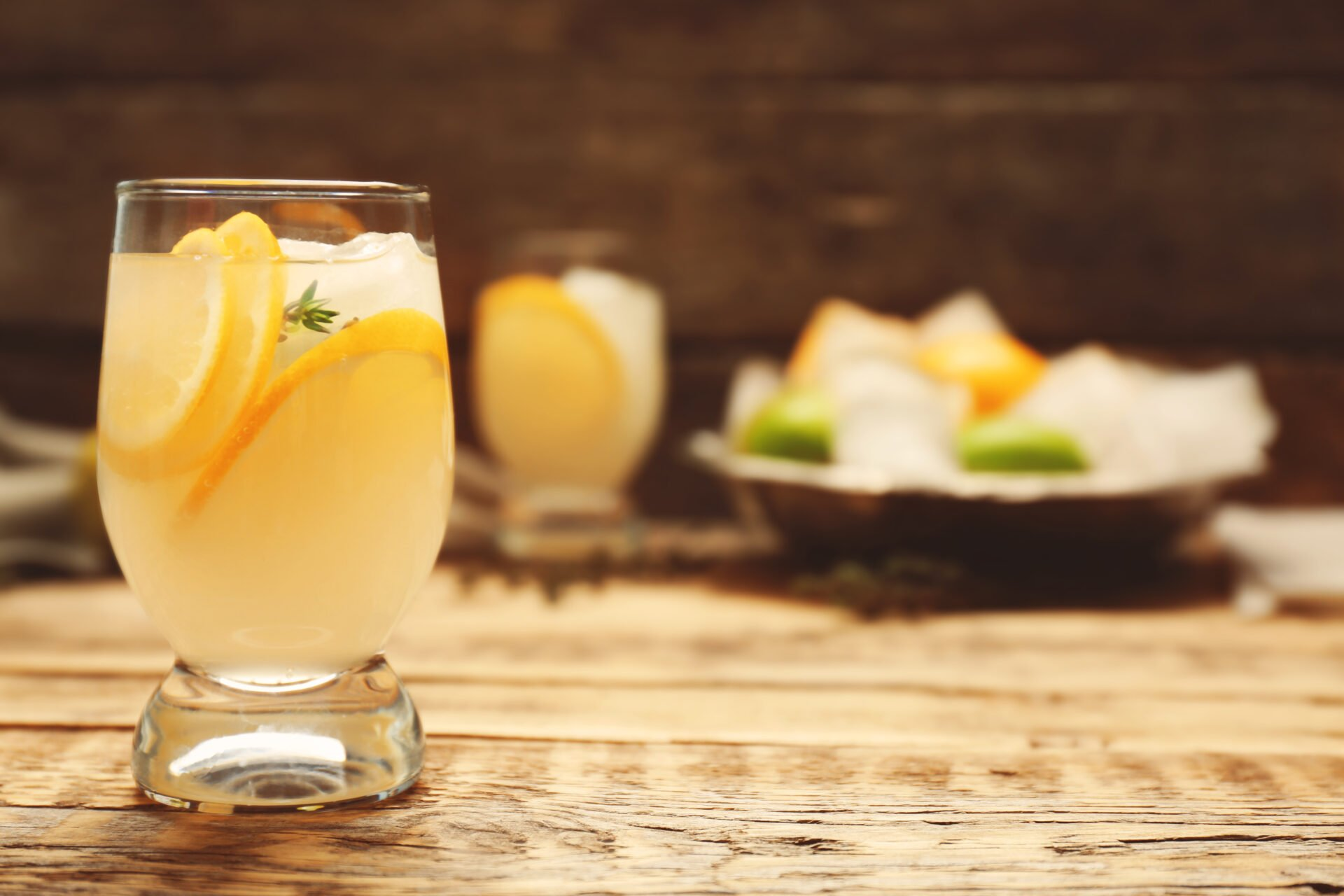 Refreshing cocktail with lemon on wooden table