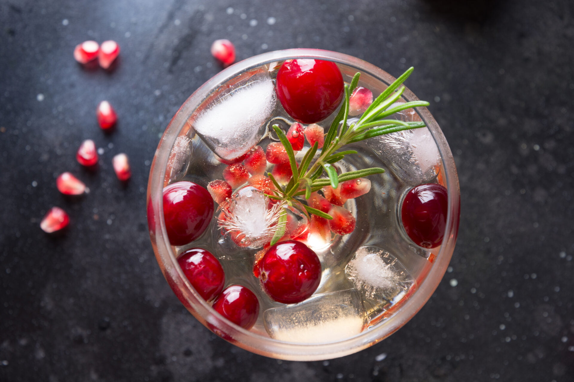Pomegranate Christmas cocktail with rosemary, club soda on black table