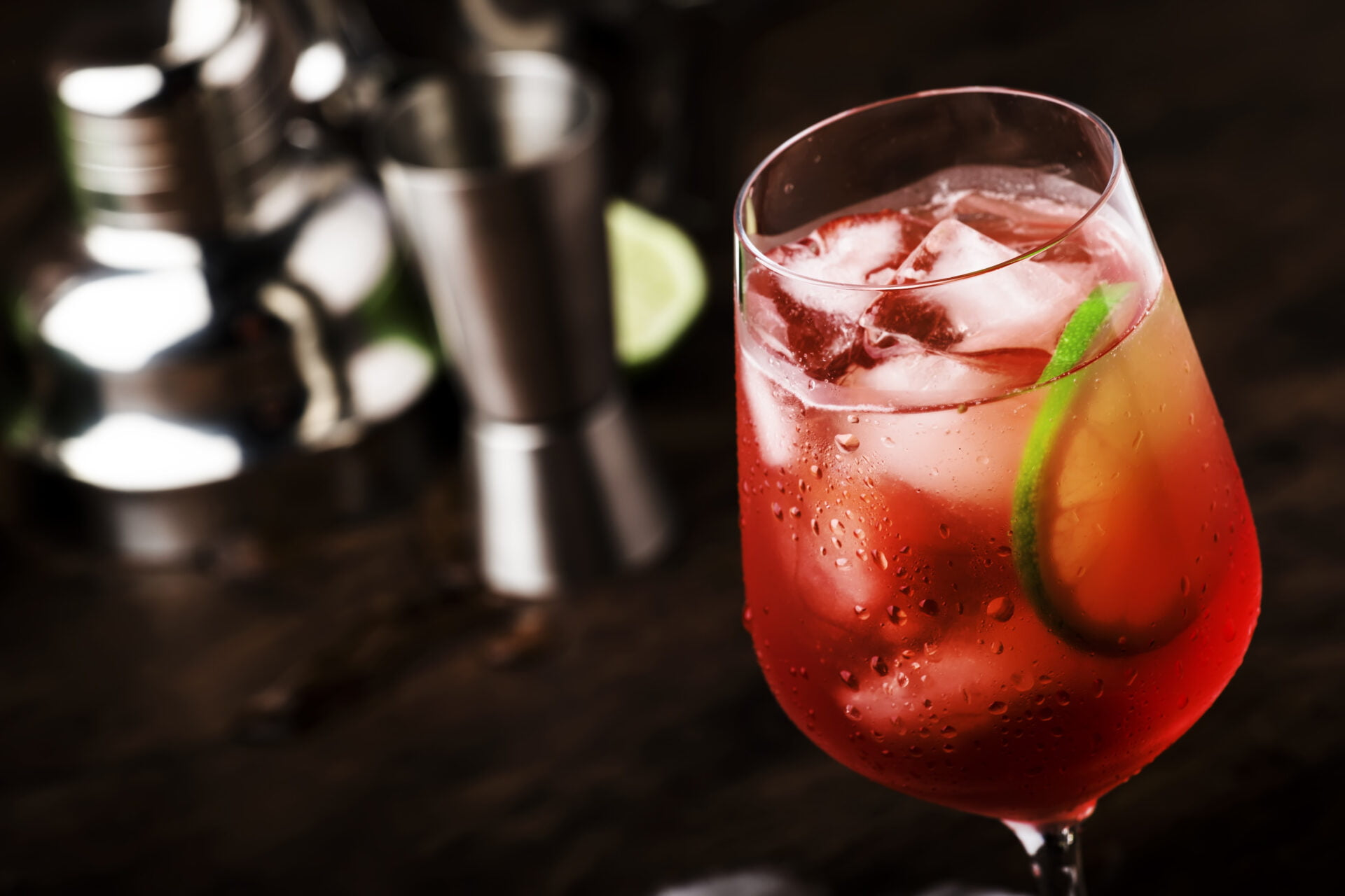 Campari tonic alcoholic cocktail with red bitter, tonic, lime and ice. Old wooden table background & bar tools