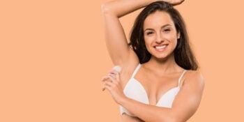 woman putting on deodorant in her bra