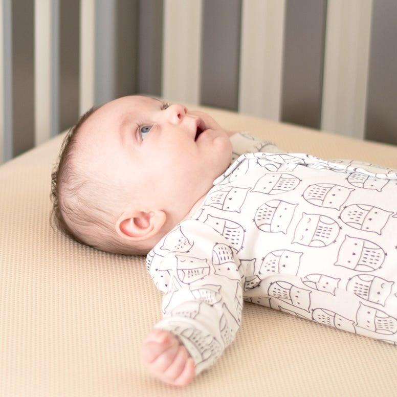 Baby sleeping on Naturepedic crib mattress