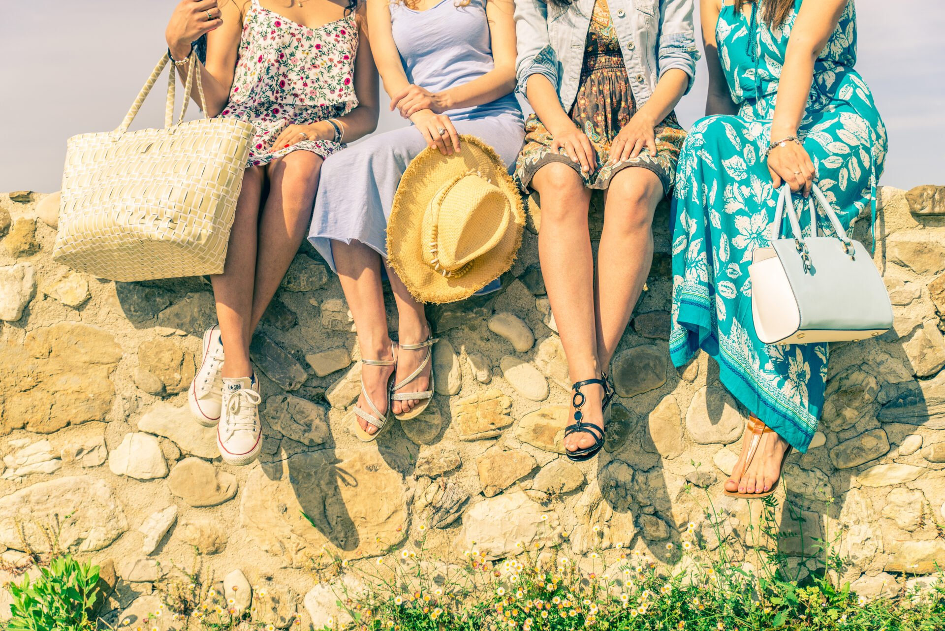 Four girlfriends sitting on a wall outdoors with spring and summer dressware - Women meeting and having fun in a countryside