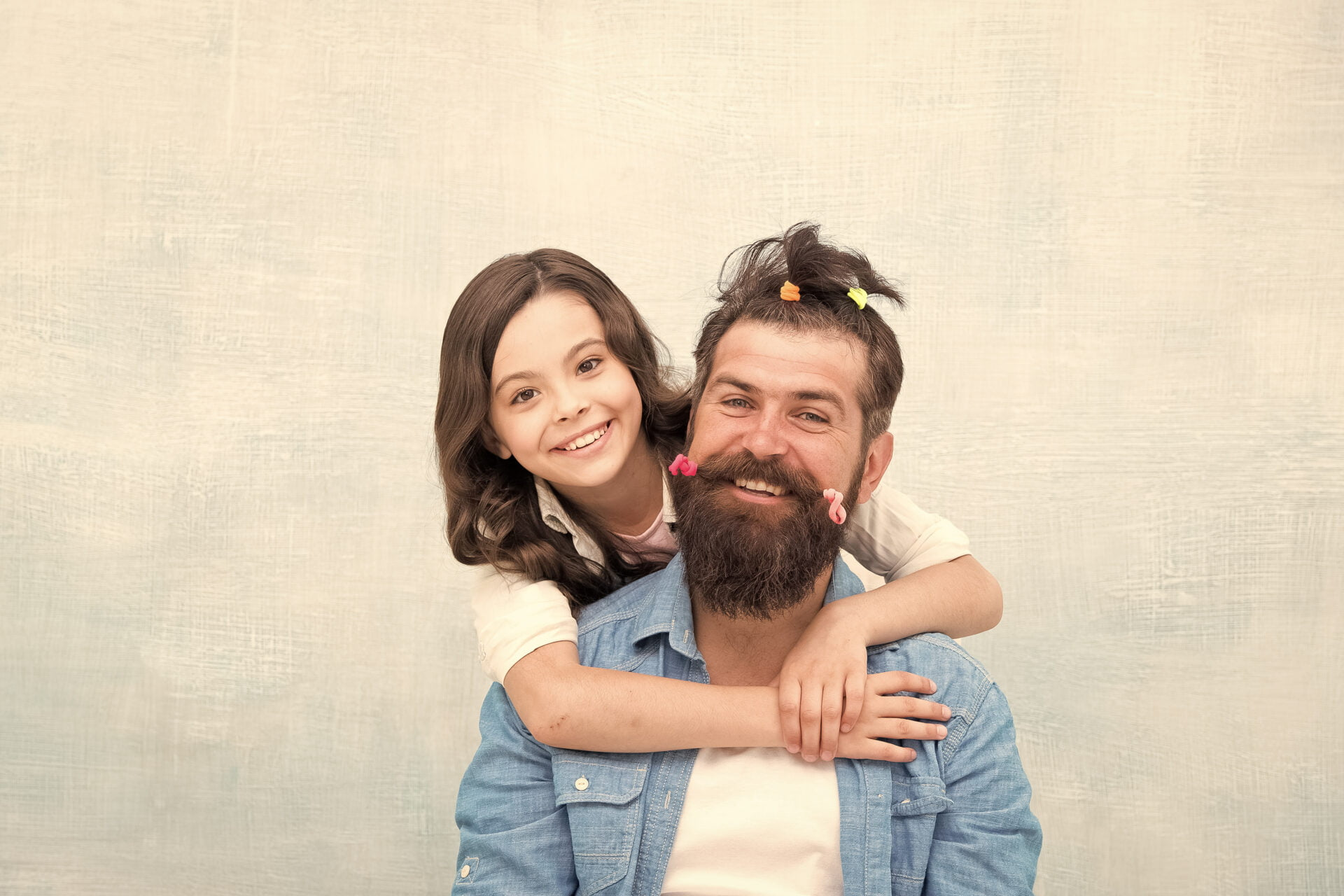 daughter gives bearded daddy a ponytail