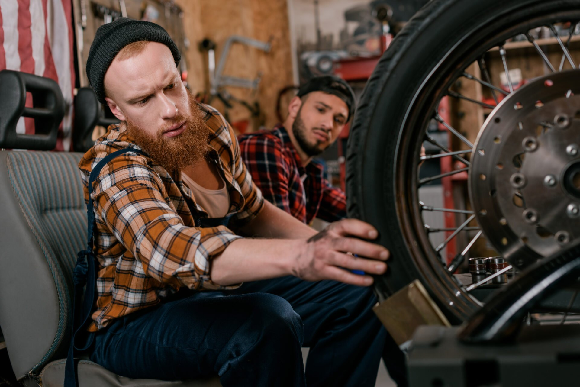 Handsome redheaded man fixing a bike in the shop