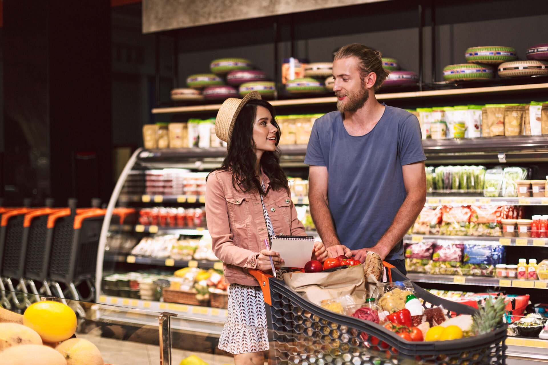 Young guy and pretty girl with shopping list in hand dreamily looking at each other with trolley full of products in modern supermarket