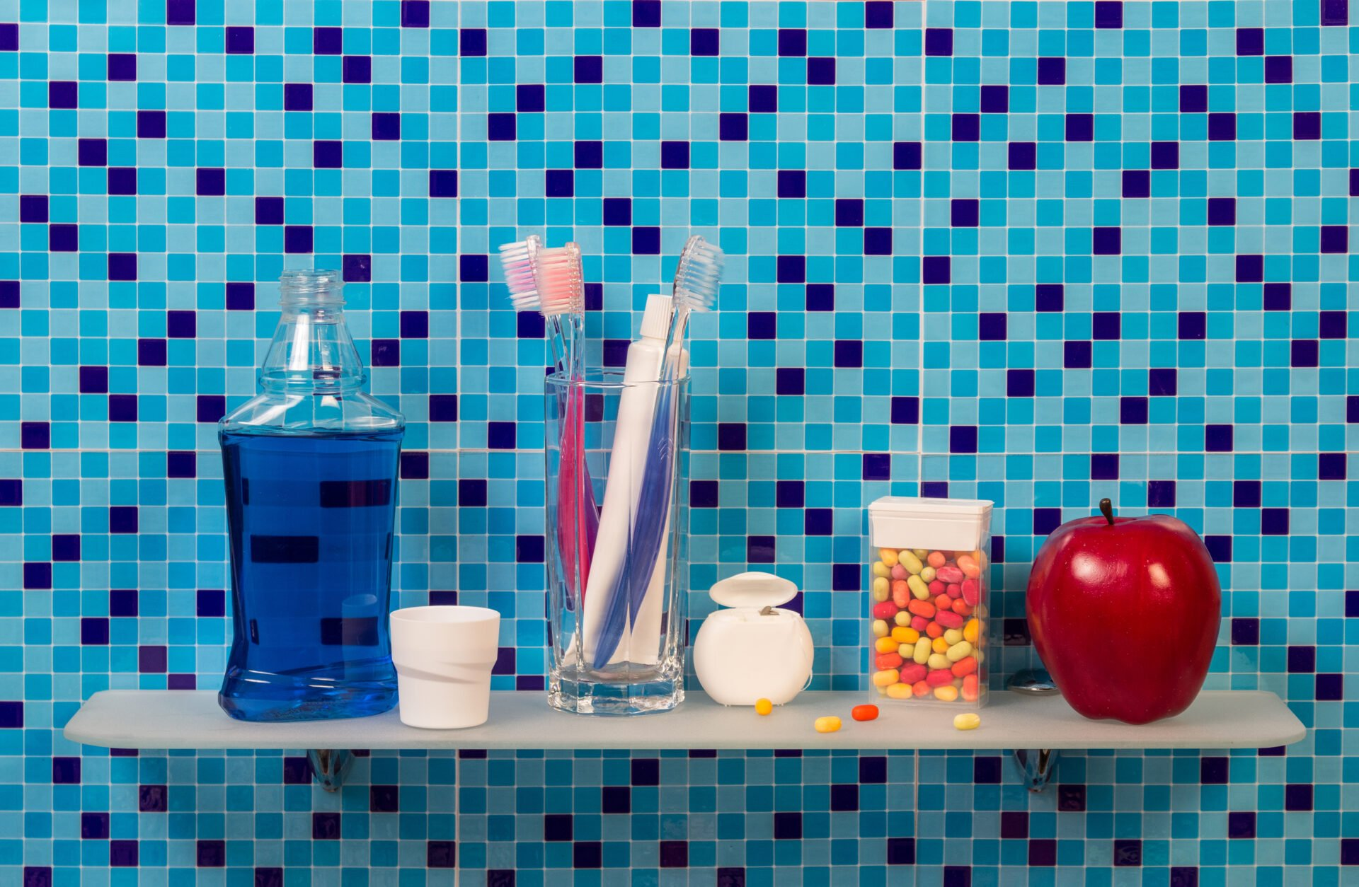 mouthwash, toothpaste, tooth brushes on a shelf in the bathroom