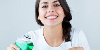 beautiful girl using mouthwash