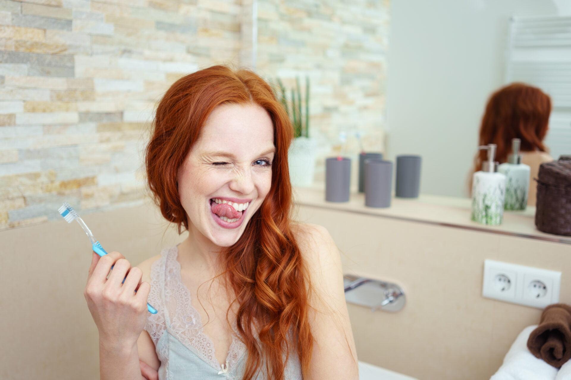 Playful redhead brushing her teeth