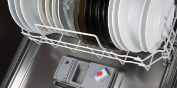 Open dishwasher with clean plates in it, focus on tabs dishwasher tabs