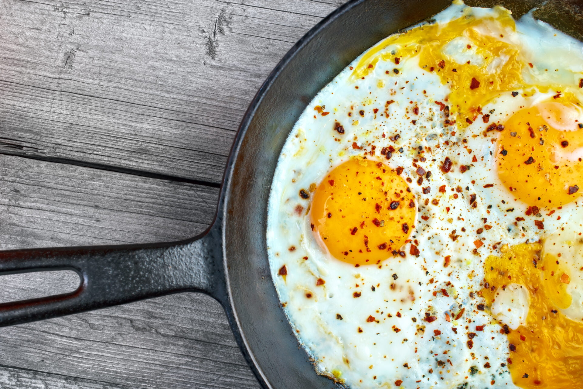 Fried eggs in cast iron frying pan on gray wooden surface